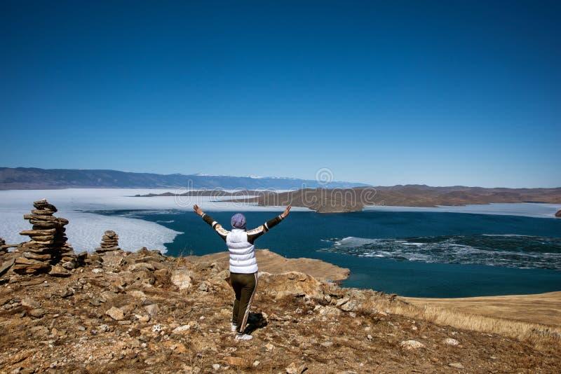 Het Weergeven boven groot mooi meer Baikal met Ijsijsschollen die op het water en het meisje drijven bevindt zich dichtbij rotsen stock afbeeldingen