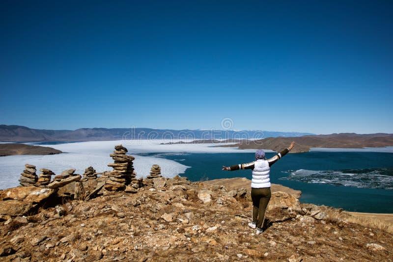 Het Weergeven boven groot mooi meer Baikal met Ijsijsschollen die op het water en het meisje drijven bevindt zich dichtbij rotsen stock foto