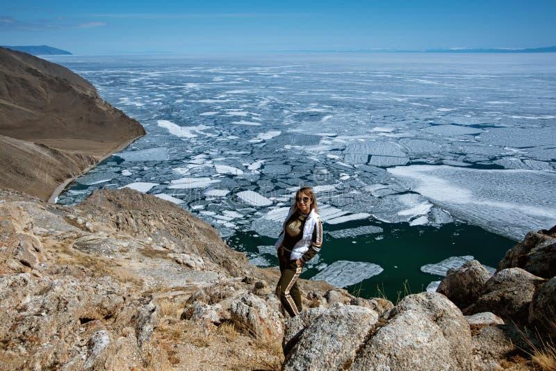 Het Weergeven boven groot mooi meer Baikal met Ijsijsschollen die op het water met meisje drijven draagt wit jasje, Rusland royalty-vrije stock foto's