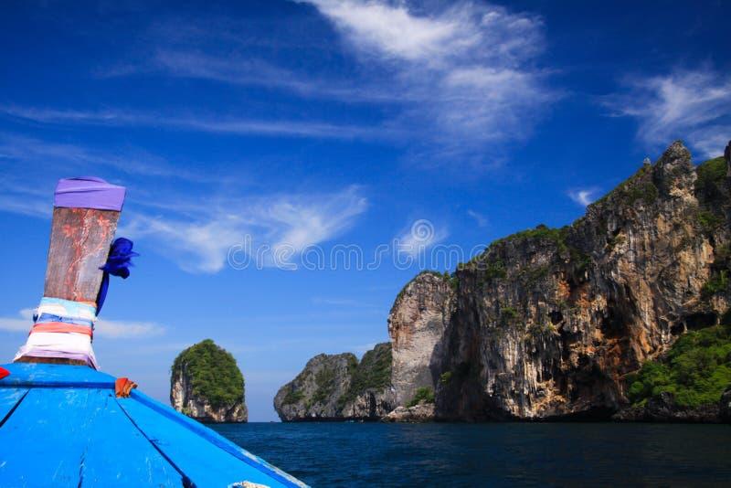 Het Weergeven op blauw verfraaide houten boog van longtailboot en rotsmuur onder blauwe hemel met weinig cirruswolken stock foto's