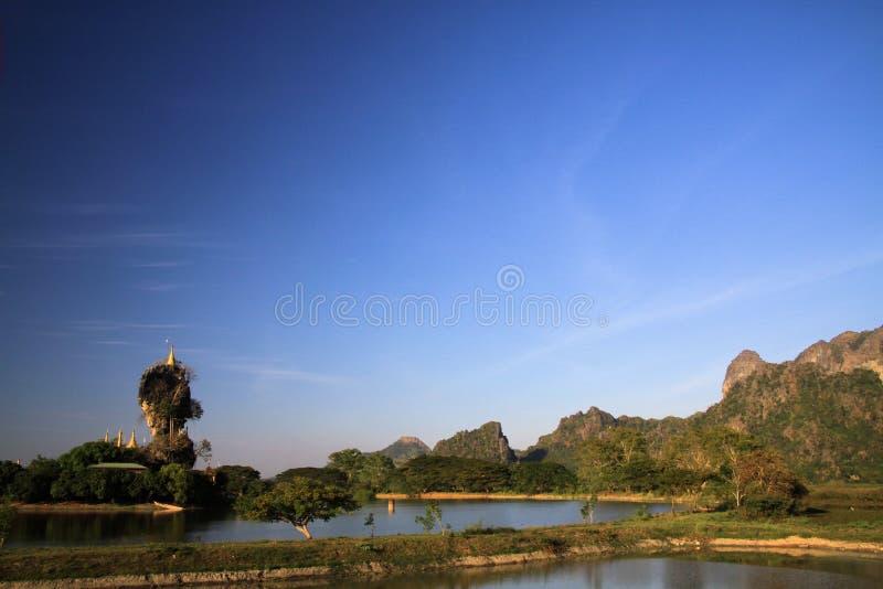 Het Weergeven op de pagode van Kyauk Kalap situeerde op hoge het toenemen rots over een meer in Hpa, Myanmar stock foto