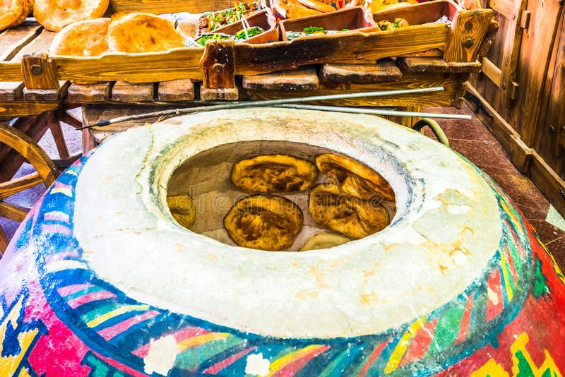 Het Weergeven op huis maakte lavash brood wordt gebakken binnen een traditionele Armeense geroepen vloeroven tonir stock fotografie
