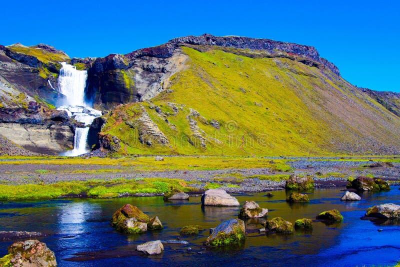 Het Weergeven over kleine rivier met keien en de stenen op water vallen tegen blauwe hemel stock afbeelding