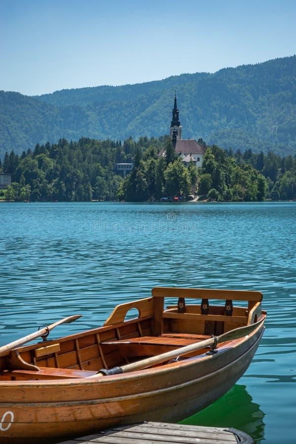 Het Weergeven over Meer tapte in Slovenië met een het roeien boot in de voorgrond af royalty-vrije stock foto's