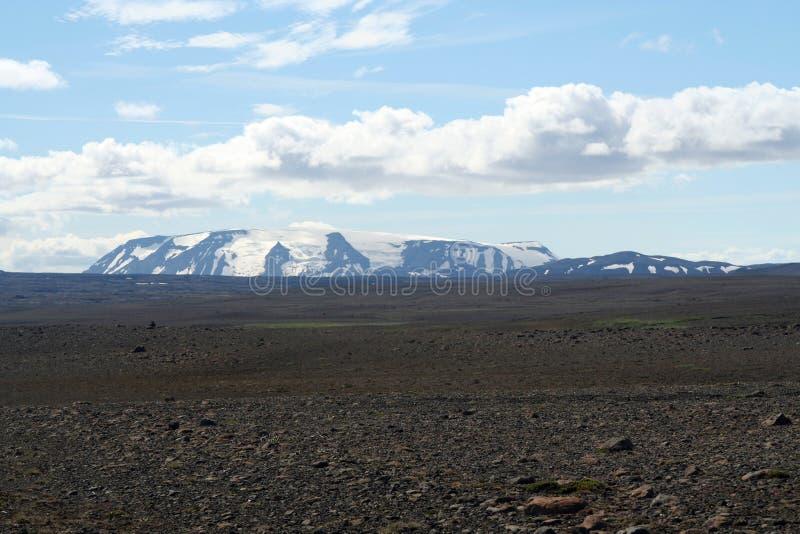 Het Weergeven over zwarte brede eindeloze zwarte onvruchtbare woestenij met sneeuw dekte bergen af - IJsland stock foto's
