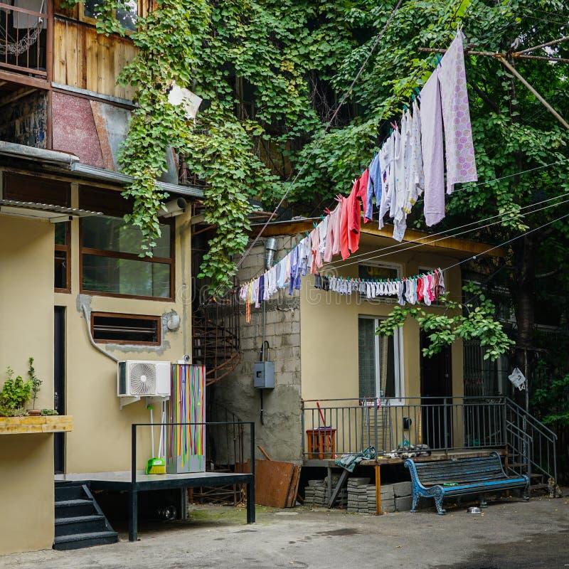 Het Weergeven van buiten het huishouden, kleren droogt op kabels op wasknijpers stock fotografie