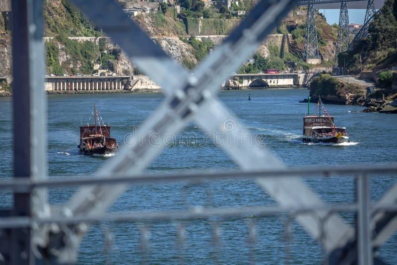 Het Weergeven van Douro-rivier en twee recreatieve boten, met toeristen, vertroebelen brug metaalstructuur op eerste plan royalty-vrije stock fotografie