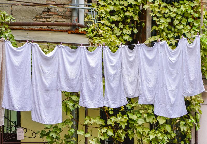 Het Weergeven van het huishouden, witte handdoeken droogt op kabels op wasknijpers royalty-vrije stock afbeeldingen
