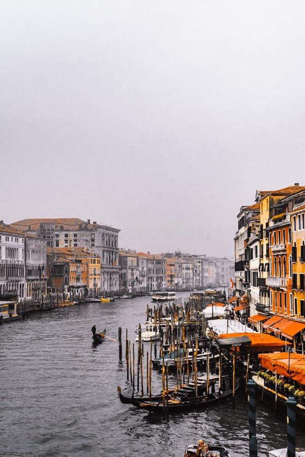 Het Weergeven van het Kanaal in Venetië van Rialto-brug, gondels kruist de rivier en de mensen genieten van hun de wintervakantie royalty-vrije stock foto