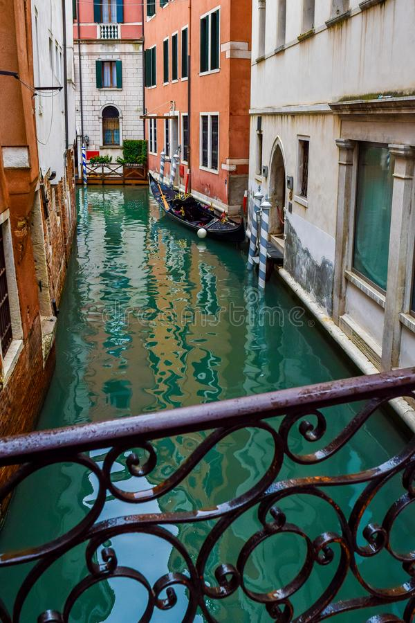 Het Weergeven van lege houten gondel dokte geparkeerd vastgelegd naast gebouwen op smal waterkanaal van brug in Venetië, Italië stock afbeeldingen