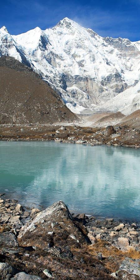 Het Weergeven zet Cho Oyu op weerspiegelend in meer - Cho Oyu-basiskamp - Everest-trek - de bergen van Nepal Himalayagebergte stock fotografie