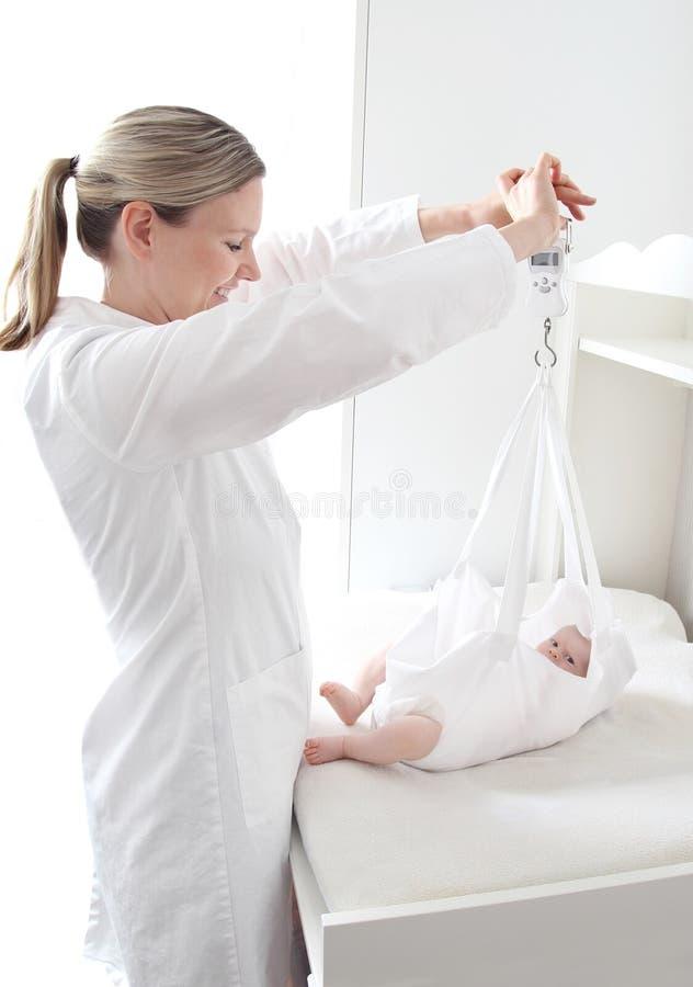 Het wegen van een pasgeboren baby stock afbeelding