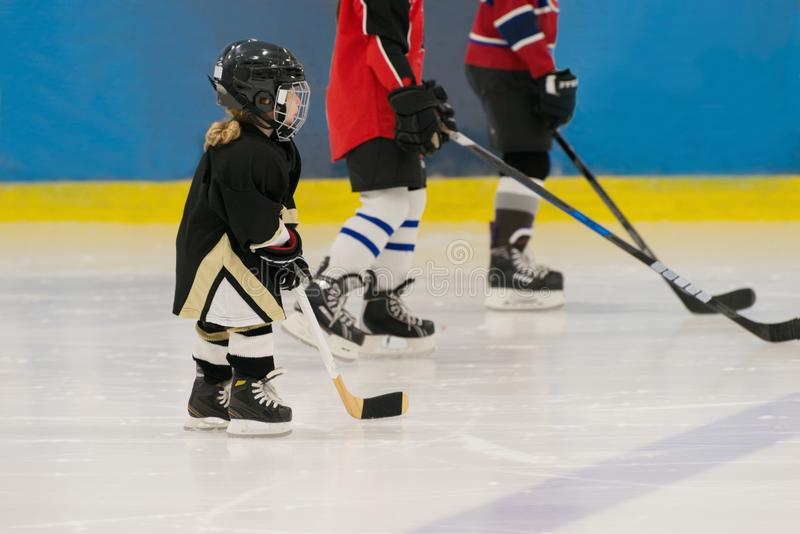 Het weinig leuke hockeymeisje is op het ijs die in volledig materiaal dragen: hockeyhelm, handschoenen, stok, vleten Cijfers van  royalty-vrije stock afbeelding