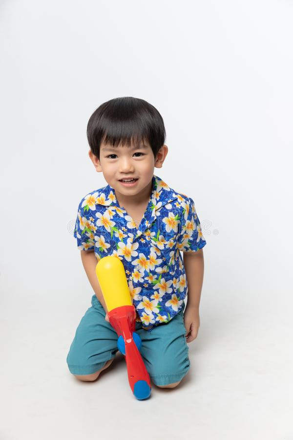 Het welkom festival van Thailand Songkran, Portret van Aziatische jongen die die bloemoverhemd dragen met waterkanon wordt geglim royalty-vrije stock foto's