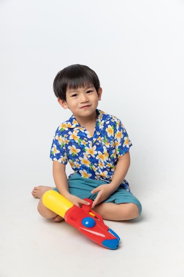 Het welkom festival van Thailand Songkran, Portret van Aziatische jongen die die bloemoverhemd dragen met waterkanon wordt geglim stock foto's