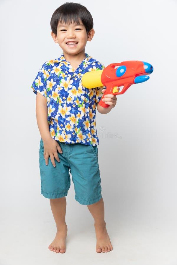 Het welkom festival van Thailand Songkran, Portret van Aziatische jongen die die bloemoverhemd dragen met waterkanon wordt geglim royalty-vrije stock foto