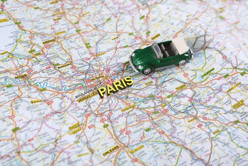 Het wensen van reis aan Parijs door auto met wegenkaart stock foto's