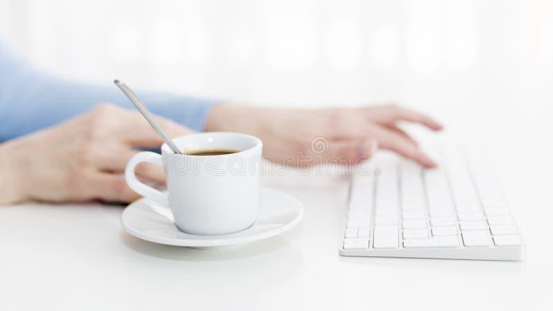 Het werk aangaande een computer met een kop van koffie stock afbeelding