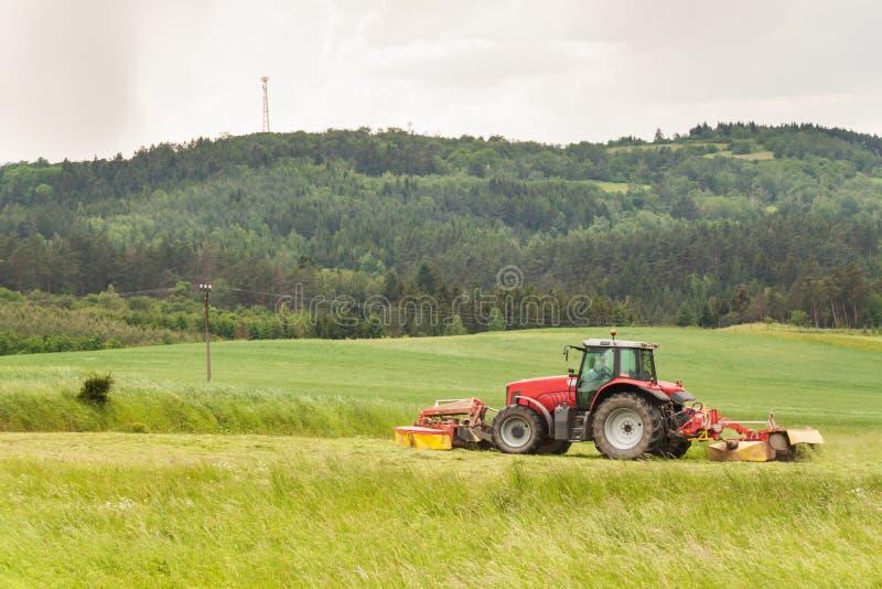 Het werk aangaande een landbouwlandbouwbedrijf Een rode tractor snijdt een weide stock foto