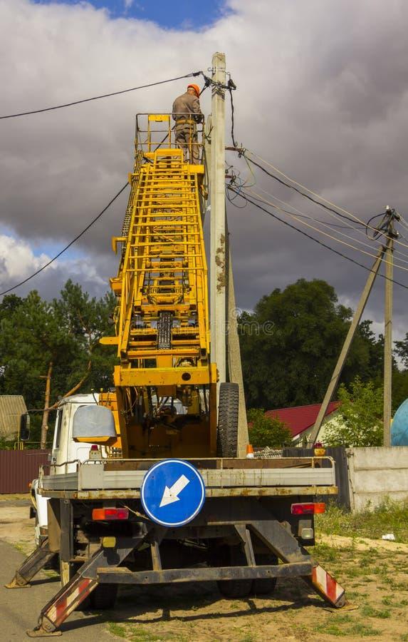 Het werk aangaande elektrische post van de de Elektricienlijnwachter van de machtspool de herstellerarbeider bij het beklimmen stock foto