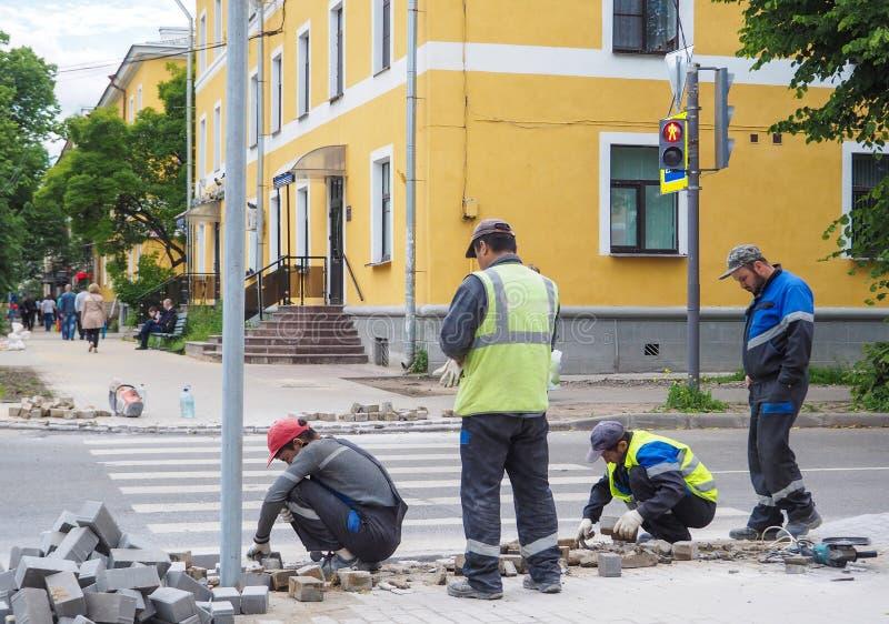 Het werk bij het leggen van de nieuwe tegel op een stadsstraat Legt de nieuwe tegel op de vloer Het bedekken in de stad Het stede royalty-vrije stock afbeelding