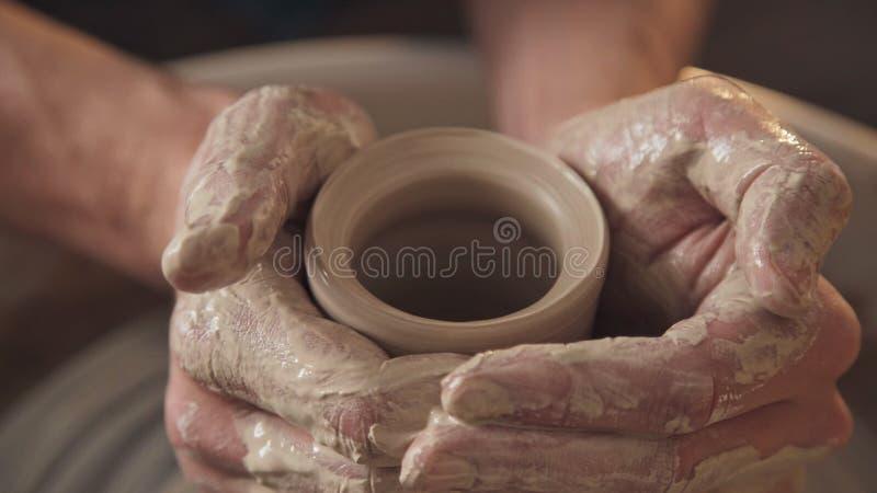 Het werk in de aardewerkworkshop: kleiwaren op het pottenbakkers` s wiel stock foto