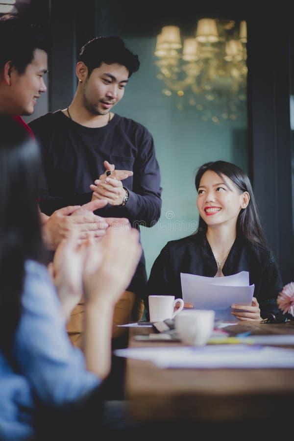 Het werk de teamgelukwens aan Aziatisch freelance vrouwenproject keurt in bureauvergaderzaal goed stock afbeeldingen