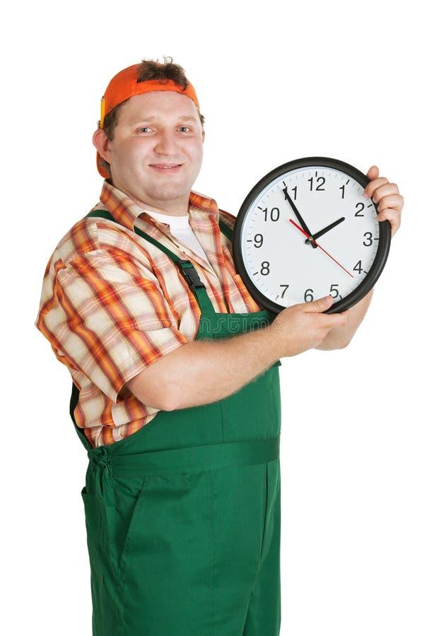 Het werk met een grote klok in de handen stock foto