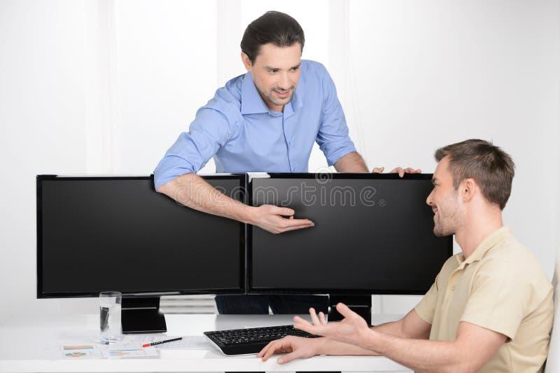 Het werk ogenblikken. Twee jonge zakenlieden die over zaken spreken wh royalty-vrije stock fotografie