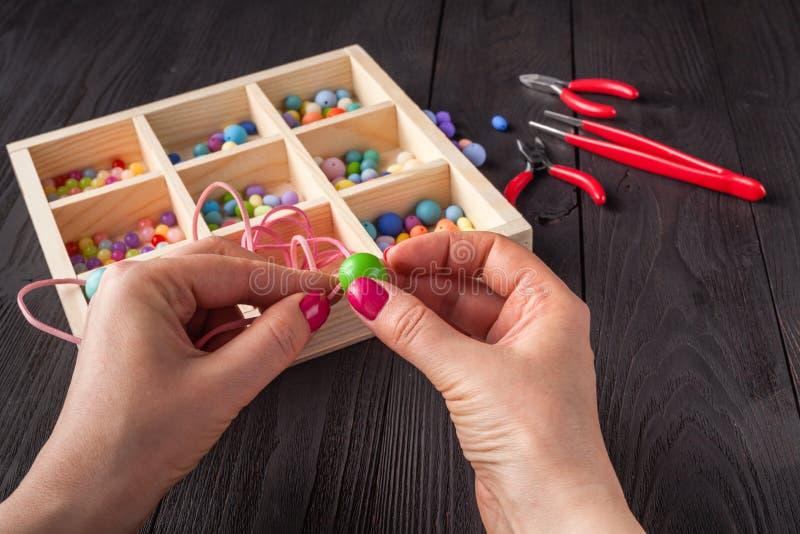 Het werk proces Handcraftconcept Creatieve vrouw die mooie parels van kleurrijke ballen maken stock afbeelding