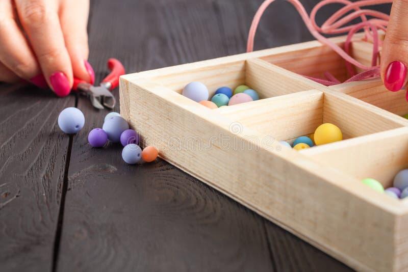 Het werk proces Handcraftconcept Creatieve vrouw die mooie parels van kleurrijke ballen maken stock foto's