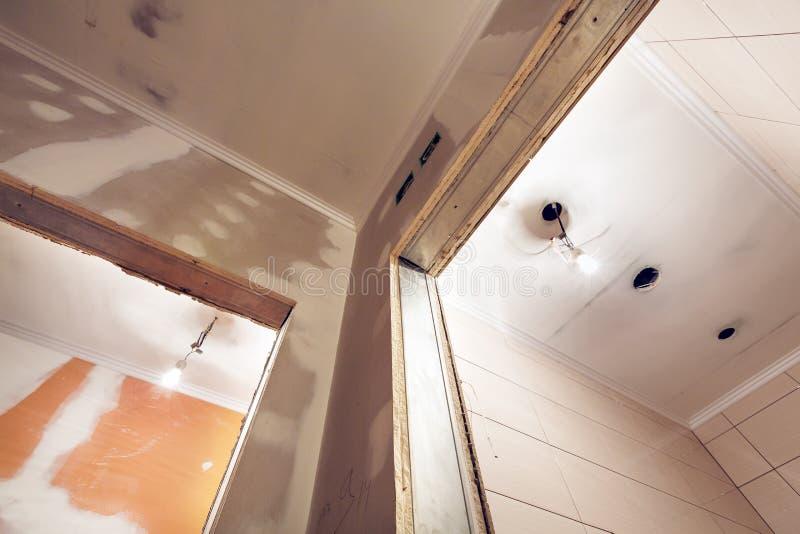 Het werk het proces om gipsplaat of drywall voor het maken van gipsmuren in flat te installeren is in aanbouw royalty-vrije stock afbeeldingen