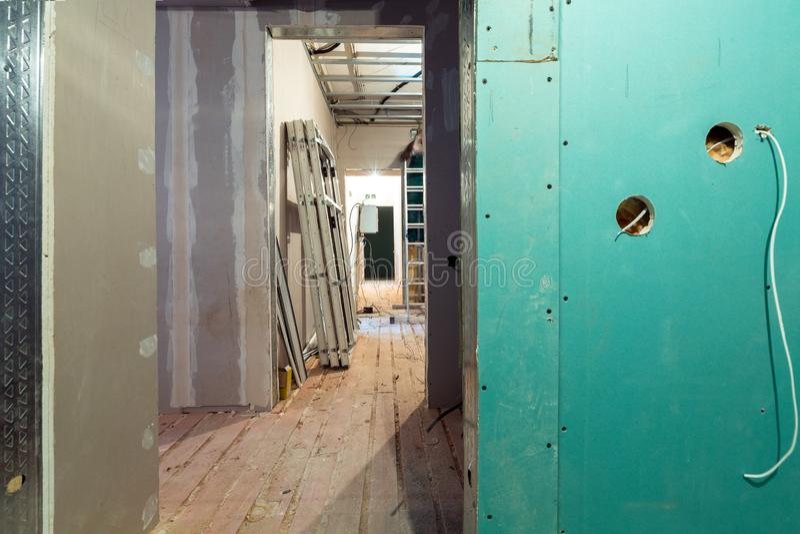 Het werk proces om kaders voor gipsplaat te installeren - drywall en bouw de hulpmiddelen in flat is onder stock afbeelding