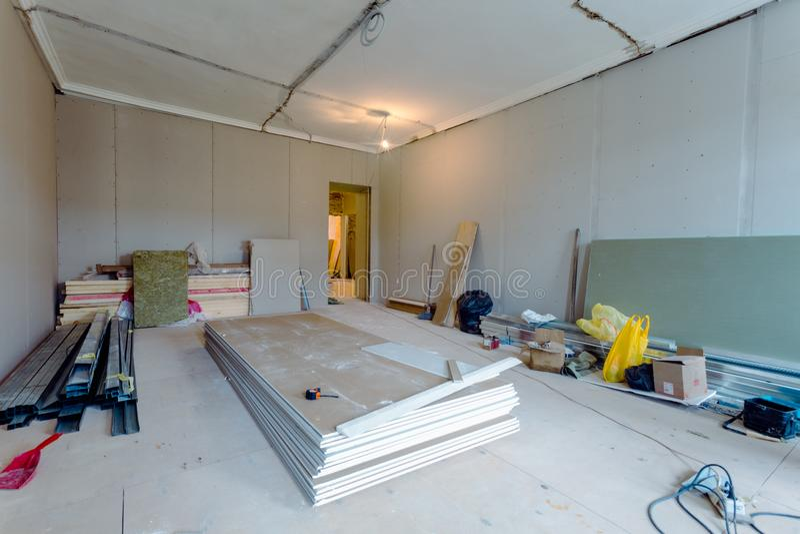 Het werk het proces om metaalkaders voor gipsplaatdrywall voor gipsmuren in flat te installeren is in aanbouw stock afbeeldingen