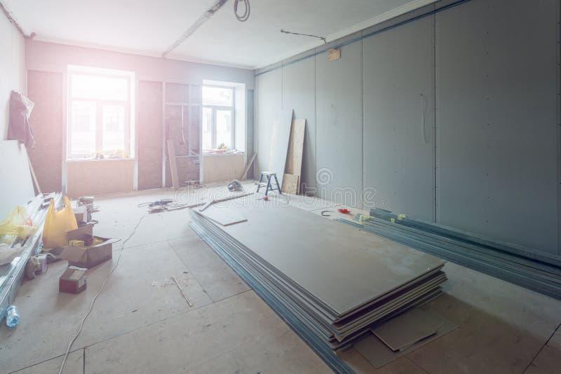 Het werk het proces om metaalkaders voor gipsplaatdrywall voor het maken van gipsmuren in flat te installeren is in aanbouw stock fotografie