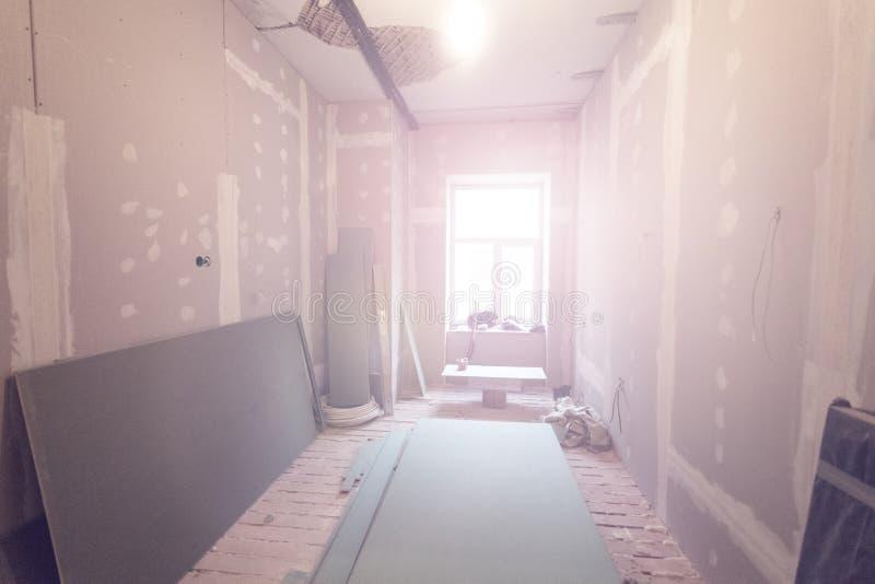 Het werk het proces om metaalkaders voor gipsplaatdrywall voor het maken van gipsmuren in flat te installeren is in aanbouw stock afbeeldingen