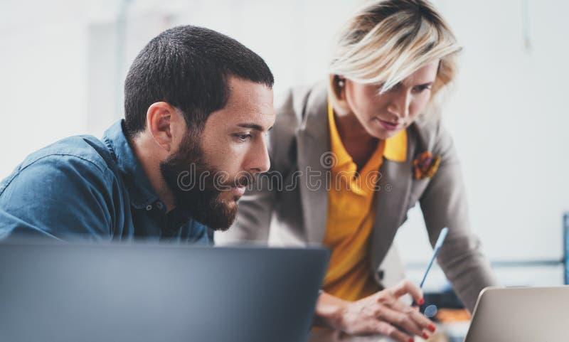 Het werk procesogenblikken Twee jonge medewerkers die bij moderne bureauzolder samenwerken stock foto's