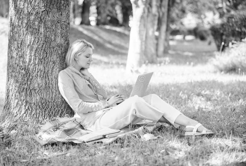 Het werk profiteert in openlucht De vrouw met laptop het computerwerk leunt in openlucht op boomboomstam Onderwijstechnologie en  royalty-vrije stock foto