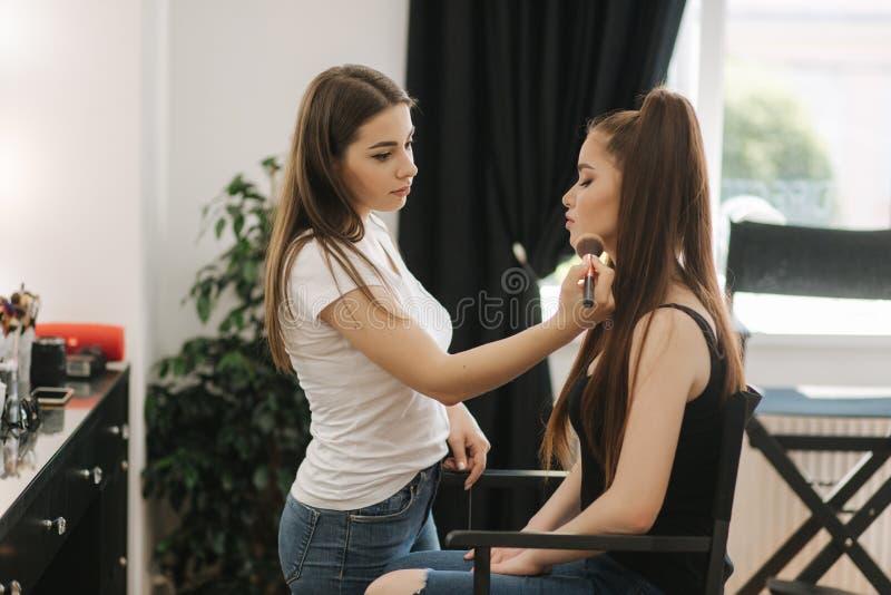Het werk van de make-upkunstenaar met model in schoonheidsstudio De manier maakt voor elegant roodharigemodel stock foto