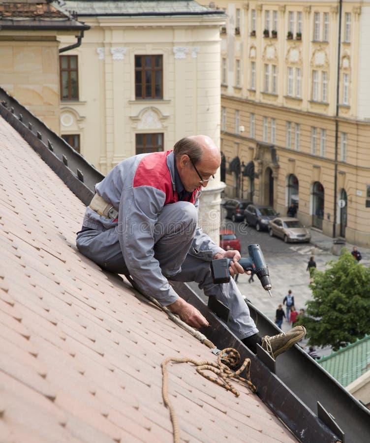 Het werk van de mens op het dak royalty-vrije stock afbeeldingen