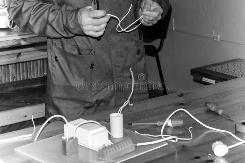 Het werk van de mensen werkend elektricien, verzamelt de elektrische kring van een grote witte straatlantaarn met draden, een rel stock afbeeldingen