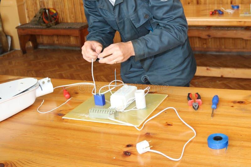 Het werk van de mensen werkend elektricien, verzamelt de elektrische kring van een grote witte straatlantaarn met draden, een rel stock afbeelding