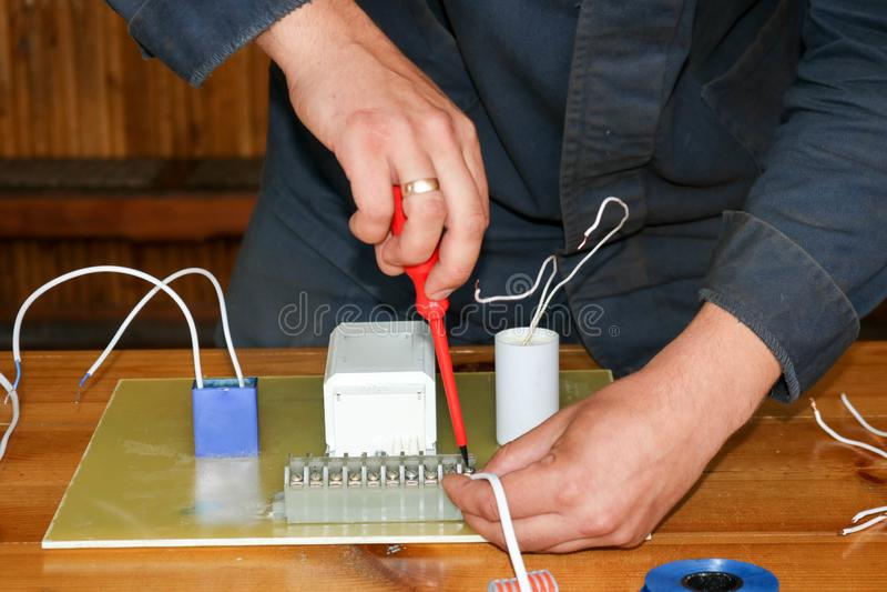 Het werk van de mensen werkend elektricien, verzamelt de elektrische kring van een grote witte straatlantaarn met draden, een rel stock foto's