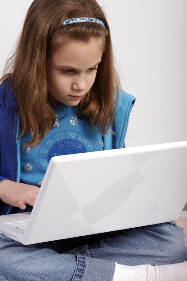 Het werk van de school aangaande haar laptop stock afbeelding
