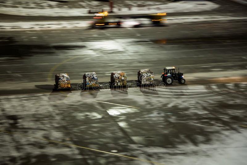 Het werk van de technische diensten bij de luchthaven De tractor is snel gelukkig verscheidene karren met de ingepakte vracht stock foto's