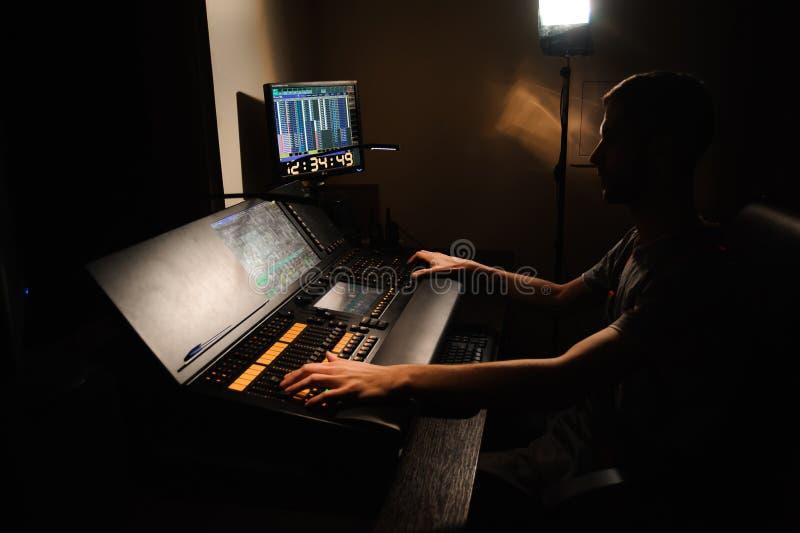 Het werk van de verlichtingsingenieur met de controle van lichtentechnici op het overleg toont Professionele lichte mixer, die co stock fotografie