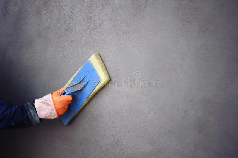 Het werk van een stukadoor door pleister op de muur toe te passen om een vlotte oppervlakte te hebben royalty-vrije stock fotografie