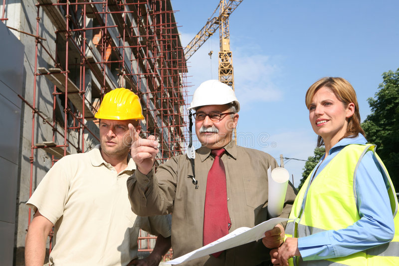 Het werk van het team bij de bouwwerf stock afbeeldingen