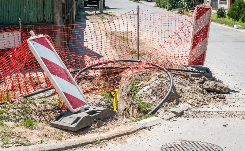 Het werk van het verkeerteken vooruit met rode en witte barrières op de straatbouwwerf in de stad en oranje veiligheidsnet voor i royalty-vrije stock foto