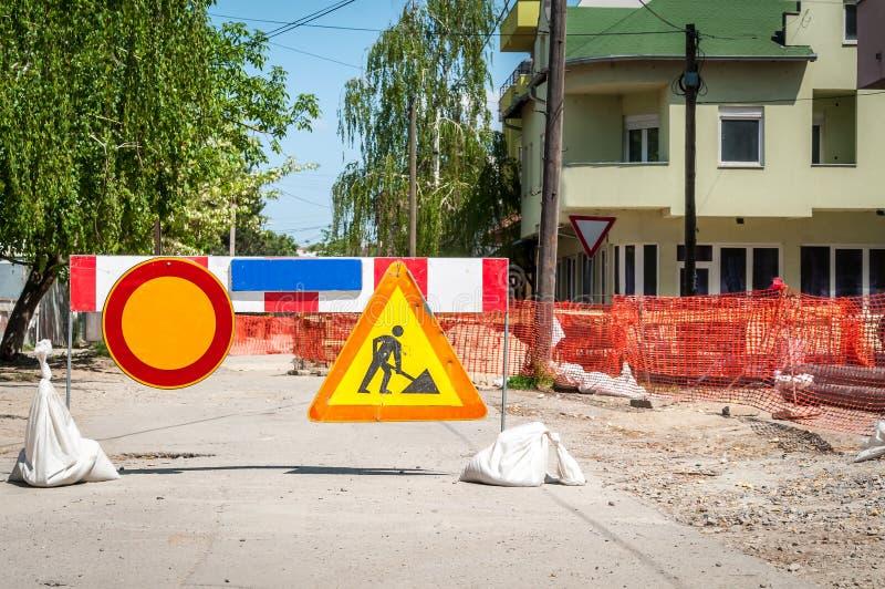 Het werk vooruit straat de wederopbouwplaats van de stadsverwarmingsinstallatiespijpleiding met teken en omheining als wegbarrica stock fotografie